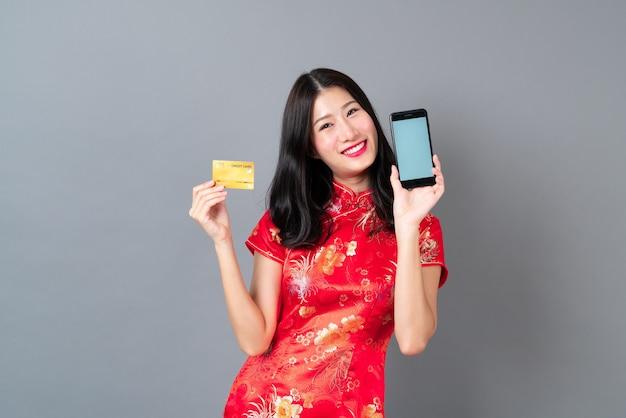 Piękna młoda azjatycka kobieta nosi czerwoną chińską sukienkę za pomocą smartfona i trzyma kartę kredytową na szarym tle