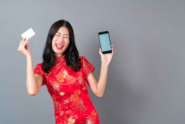 Piękna młoda azjatycka kobieta nosi czerwoną chińską sukienkę za pomocą smartfona i trzyma kartę kredytową