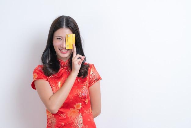 Piękna młoda azjatycka kobieta nosi czerwoną chińską tradycyjną sukienkę, trzymając kartę kredytową na chiński nowy rok z białą ścianą i miejscem na kopię