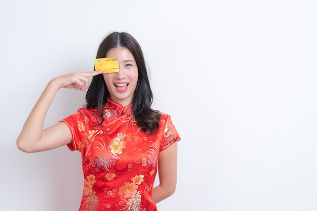 Piękna Młoda Azjatycka Kobieta Nosi Czerwoną Chińską Tradycyjną Sukienkę, Trzymając Kartę Kredytową Na Chiński Nowy Rok Z Białą ścianą I Miejscem Na Kopię Premium Zdjęcia