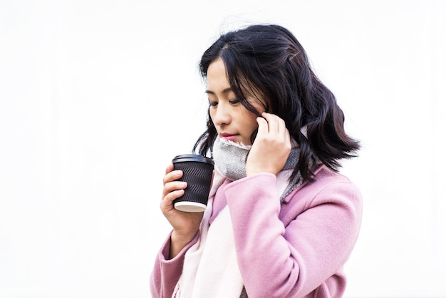 Piękna młoda azjatycka kobieta pije gorący napój z jednorazowego kubka papierowego na zewnątrz na białym tle. spójrz w dół. dziewczyna dotyka jej włosów.