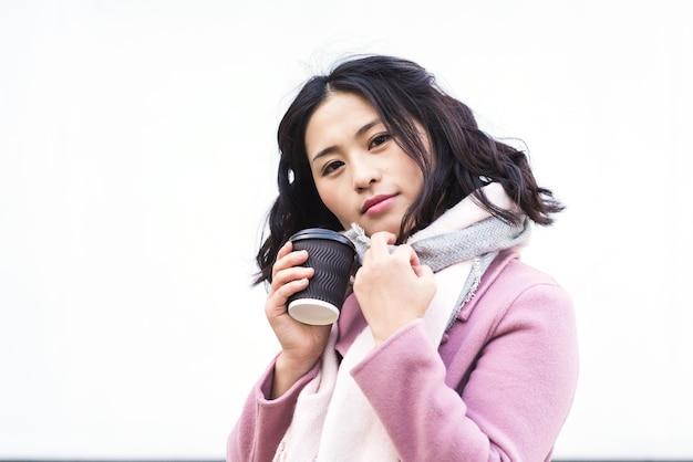 Piękna młoda azjatycka kobieta pije gorący napój z jednorazowego kubka papierowego na zewnątrz na białym tle