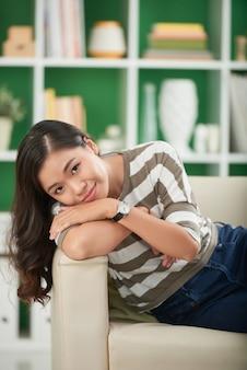 Piękna młoda azjatycka kobieta relaksuje na leżance z jej głową na przedramieniu