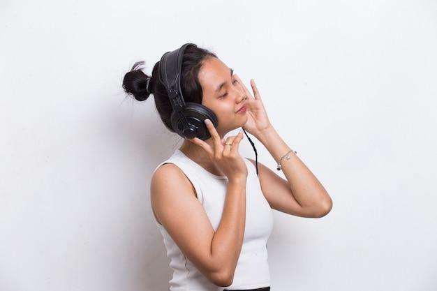 Piękna młoda azjatycka kobieta słucha muzyki na białym tle