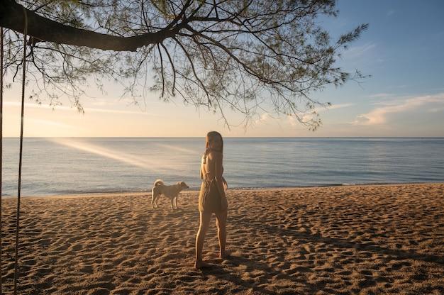 Piękna młoda azjatycka kobieta stojąca z bezpańskim psem i słońcem na plaży rano