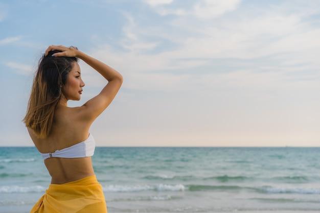 Piękna młoda azjatycka kobieta szczęśliwa relaksuje odprowadzenie na plażowym pobliskim morzu.