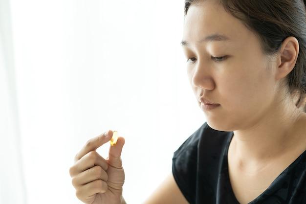 Piękna młoda azjatycka kobieta trzyma kapsułkę oleju rybnego na dłoni z bliska. produkt odżywczo-witaminowy. tabletka soft gel na kobiecej dłoni.