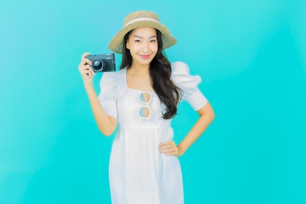 Piękna młoda azjatycka kobieta używa aparatu na niebiesko