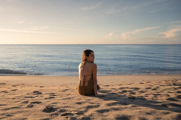 Piękna młoda azjatycka kobieta w strojach kąpielowych siedzi i opala się na plaży ze słońcem rano