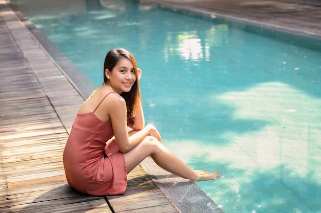 Piękna młoda azjatycka kobieta w sukni siedzącej przy basenie w tropikalnym kurorcie