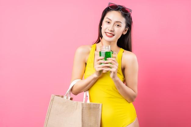 Piękna młoda azjatycka kobieta w żółtym stroju kąpielowym, torbie i kapeluszu z szerokim rondem, pozowanie na różowej ścianie