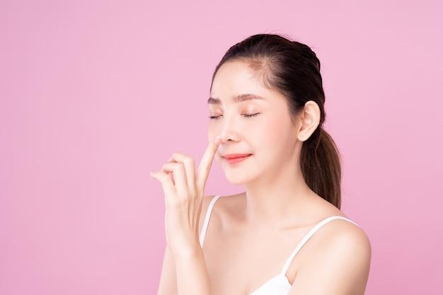 Piękna młoda azjatycka kobieta z czystą świeżą białą skórą delikatnie dotykającą własnego nosa palcami w urodzie.