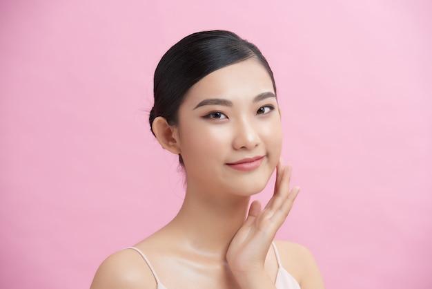 Piękna młoda azjatycka kobieta z czystą, świeżą białą skórą delikatnie dotykającą własnej twarzy w pozie piękna.