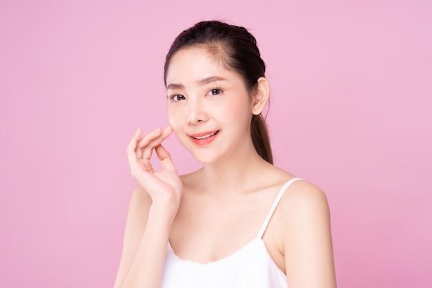 Piękna młoda azjatycka kobieta z czystą świeżą białą skórą delikatnie dotykającą własnej twarzy w pozie piękna.