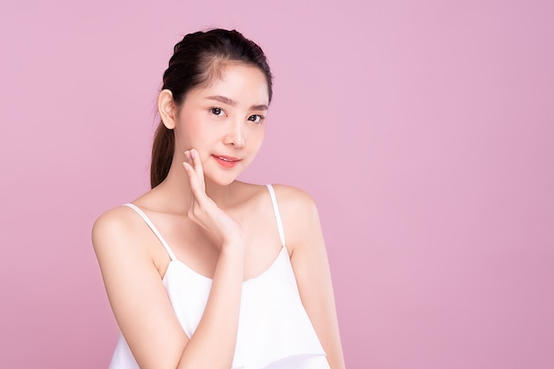 Piękna młoda azjatycka kobieta z czystą świeżą białą skórą delikatnie dotykającą własnej twarzy w urodzie.