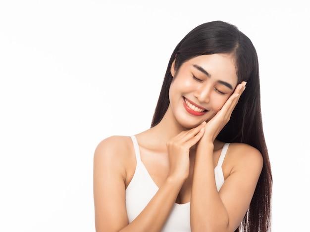 Piękna młoda azjatycka kobieta z czystą świeżą skórą i rękami dotyka twarz