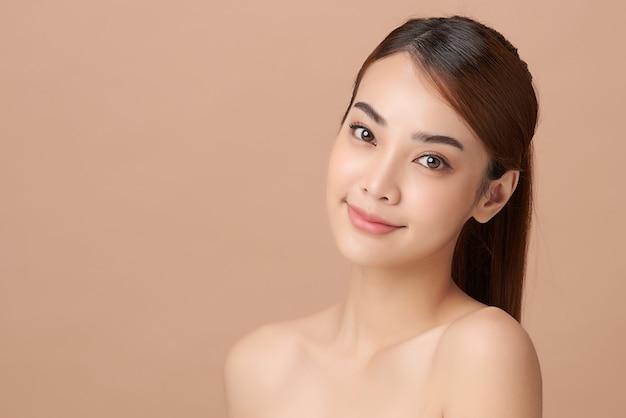 Piękna młoda azjatycka kobieta z czystą, świeżą skórą na beżowym tle, pielęgnacja twarzy, zabiegi na twarz, kosmetologia, uroda i spa, portret azjatyckich kobiet.
