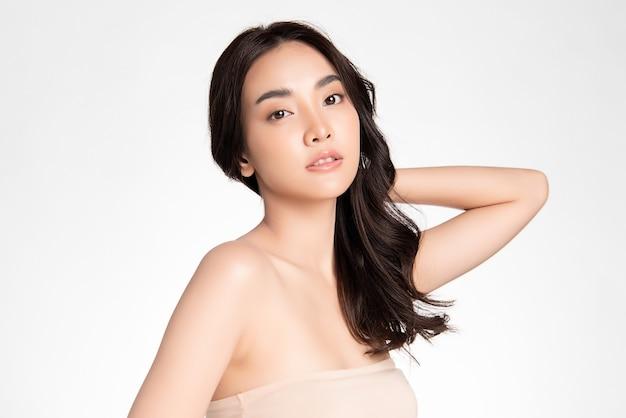 Piękna młoda azjatycka kobieta z czystą, świeżą skórą na białej ścianie, pielęgnacja twarzy, zabieg na twarz, kosmetologia, uroda i spa, portret azjatyckich kobiet