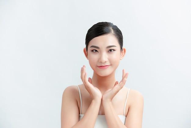 Piękna młoda azjatycka kobieta z czystą świeżą skórą na białej ścianie