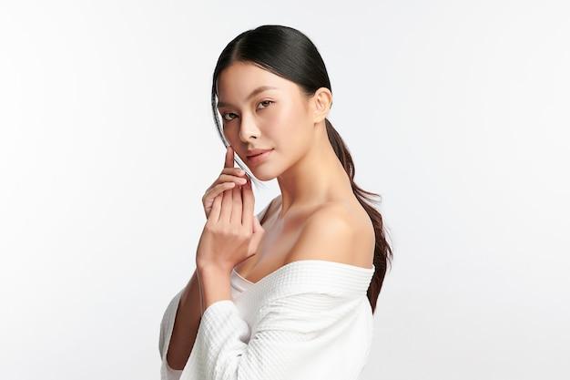 Piękna młoda azjatycka kobieta z czystą, świeżą skórą na białym tle pielęgnacja twarzy zabieg na twarz