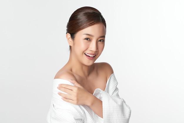 Piękna młoda azjatycka kobieta z czystą, świeżą skórą na białym tle