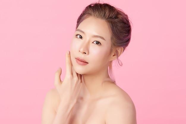 Piękna młoda azjatycka kobieta z czystą, świeżą skórą, na różowym tle, pielęgnacja twarzy, zabieg na twarz. kosmetologia, uroda