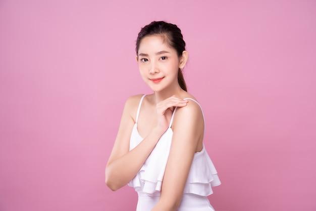 Piękna młoda azjatycka kobieta z czystym świeżym białej skóry miękkim dotyka ramieniem w piękno pozie. dziewczyna ono uśmiecha się w odosobnionym tle. reklama zabiegów na twarzy, kosmetyków, makijażu i chirurgii