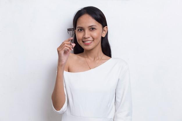 Piękna młoda azjatycka kobieta z zalotką na białym tle