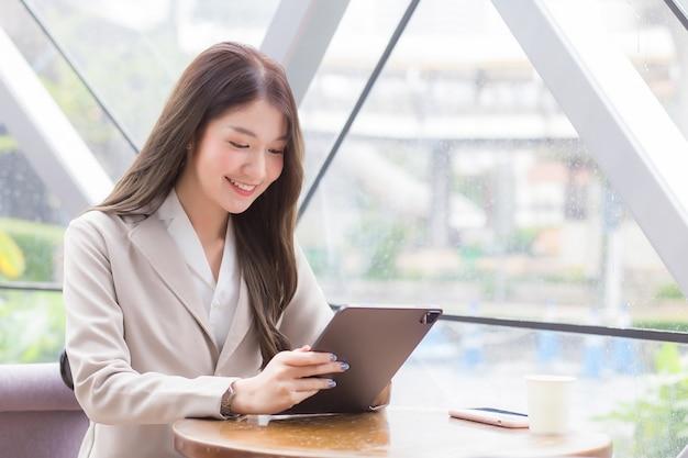 Piękna młoda azjatycka profesjonalna biznesowa kobieta w kremowym garniturze patrzy na tablet lub notatnik w dłoniach, gdy siedzi szczęśliwy uśmiech, pracując w kawiarni wśród biznesowych deseń