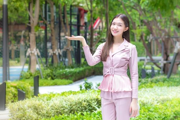 Piękna młoda azjatycka profesjonalna biznesowa kobieta z długimi włosami na sobie różową koszulę uśmiecha się na świeżym powietrzu w ogrodzie przed biurem, jednocześnie rozkładając ręce, aby zaprezentować coś z tła drzew