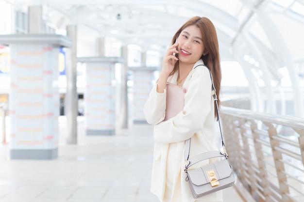 Piękna młoda azjatycka profesjonalna kobieta pracująca w białym garniturze uśmiecha się i dzwoni do klientów w biurze, podczas gdy ona trzyma tablet i torbę w dłoniach w szczęśliwy dzień roboczy z budynkami biznesowymi