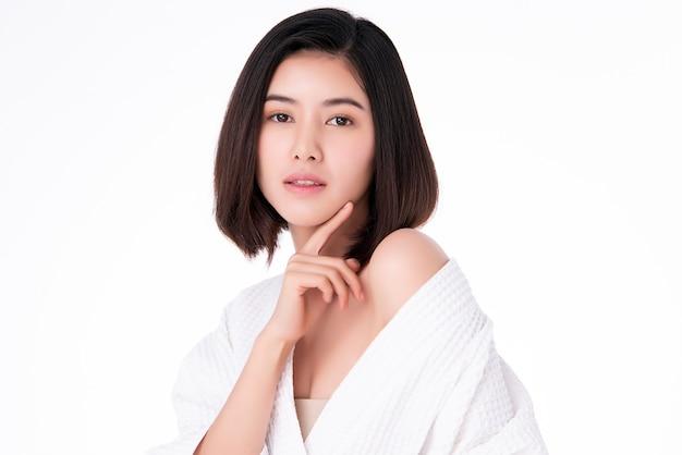 Piękna młoda azjatykcia kobieta dotyka jej czystą twarz z świeżą zdrową skórą, odizolowywającą na biel ścianie, piękno kosmetykach i twarzowego traktowania pojęciu