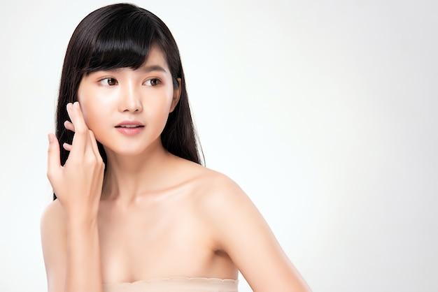 Piękna młoda azjatykcia kobieta dotyka jej czystą twarz z świeżymi zdrowych skóry piękna kosmetykami i twarzy traktowania pojęciem
