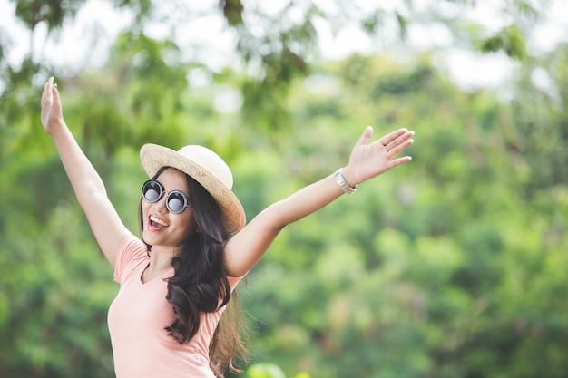 Piękna młoda azjatykcia kobieta jest ubranym wokoło kapeluszu na parku