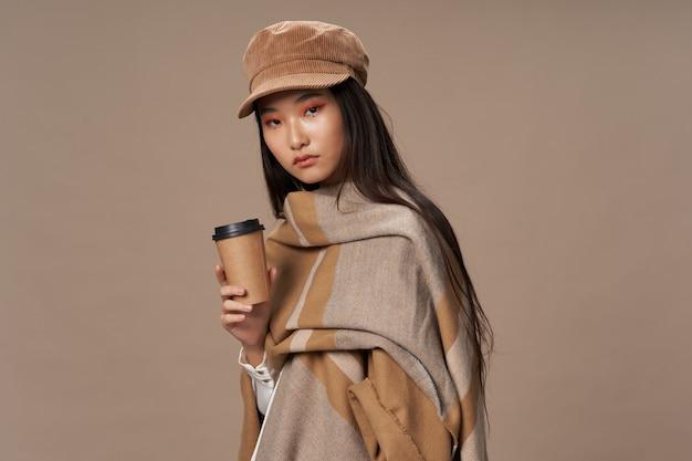 Piękna młoda azjatykcia kobieta pozuje w eleganckim odziewa