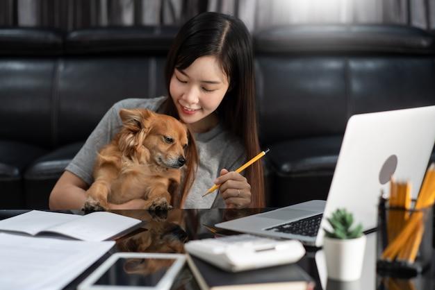Piękna młoda azjatykcia kobieta pracuje zdalnie od domu i ono uśmiecha się podczas gdy kłamający, ma dobre związki zz śmiesznym asystenta psa zwierzęciem domowym, praca domowa migdali pojęcie.