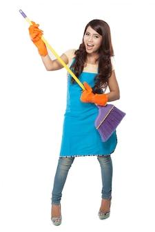 Piękna młoda azjatykcia kobieta trzyma miotłę, używa mnie jak gitarę
