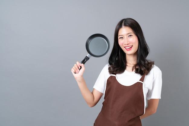 Piękna młoda azjatykcia kobieta ubrana w fartuch ręką trzymającą czarną patelnię