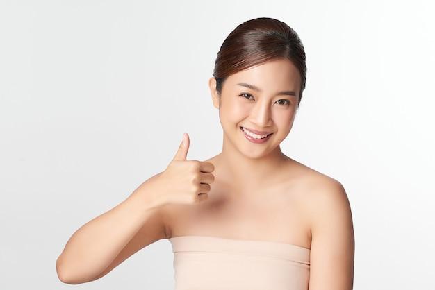 Piękna młoda azjatykcia kobieta z czystą, świeżą skórą na białym z kciukiem do góry