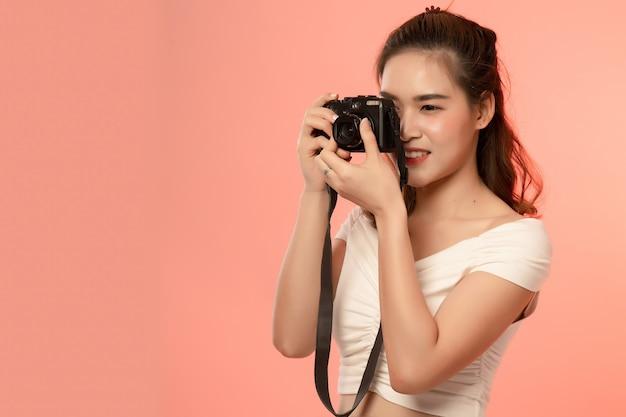 Piękna młoda azjatykcia kobieta z kamerą odizolowywającą nad menchiami. żeński fotograf w akci pracuje w studiu.