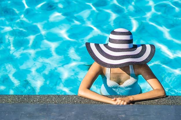 Piękna młoda azjatykcia kobieta z kapeluszem w pływackim basenie dla podróży i wakacje