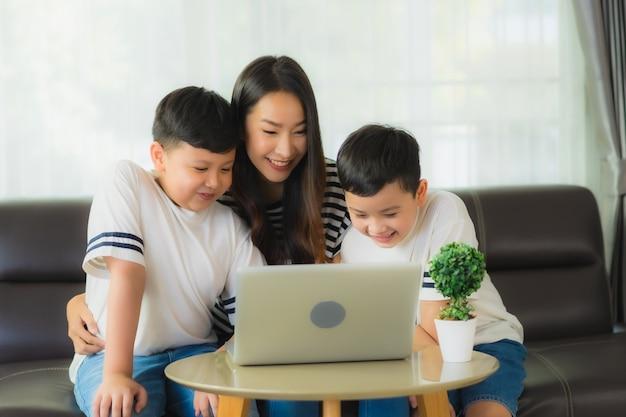 Piękna młoda azjatykcia kobiety mama z jej dwa synami używa laptop na kanapie