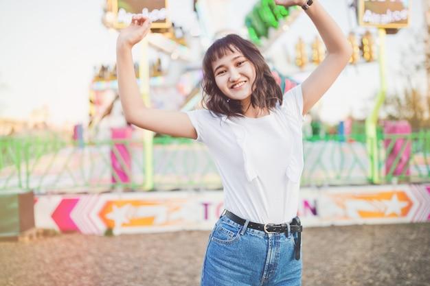 Piękna młoda azjatykcia millennial dziewczyna w parku rozrywki, ono uśmiecha się. skopiuj miejsce