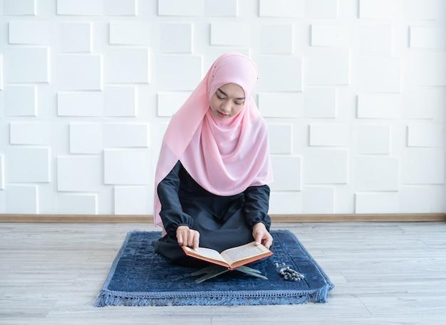 Piękna młoda azjatykcia muzułmańska kobieta czyta koran