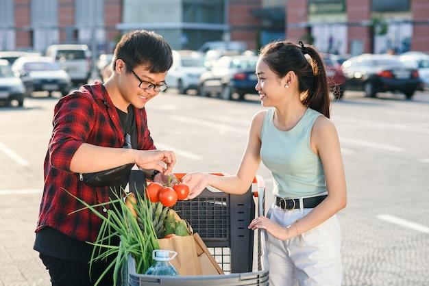 Piękna młoda azjatykcia para sprawdza kupującego jedzenie w wózek na zakupy blisko dużego sklepu