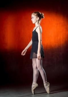 Piękna młoda balerina tańczy w studio na ciemnym tle. mały tancerz. tancerz baletowy