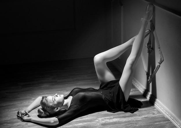 Piękna młoda balerina tańczy z baletową spódniczką w studio sylwetka na białym tle
