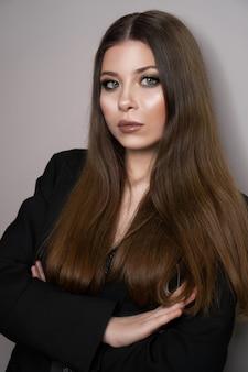 Piękna młoda biała dziewczyna z bliska w czarnej kurtce na szarym tle. wizażystka, salon kosmetyczny, magazyn