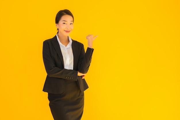 Piękna młoda biznesowa azjatykcia kobieta wskazuje strona z szczęśliwym uśmiechem