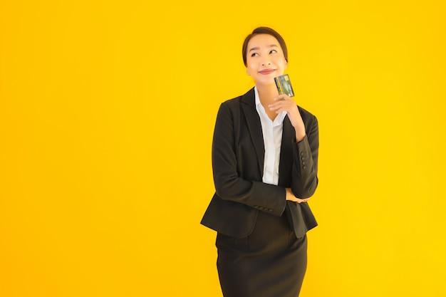 Piękna młoda biznesowa azjatykcia kobieta z kartą kredytową
